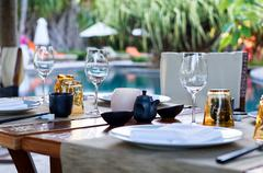 table place settings at poolside asian restaurant - stock photo