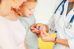 Doctor taking blood test from small patient. Stock Photos