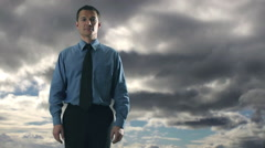 Businessman checks watch, clouds moving in background. - stock footage