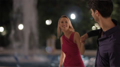 Couple walking on the street in town at night. Stock Footage