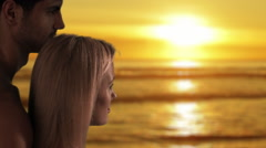 Couple gazing at sun setting over the ocean. Stock Footage