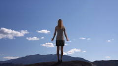Woman lifting her arms in praise on mountain. Stock Footage