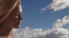 Woman's face with clouds in the background. Stock Footage