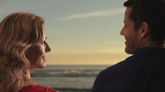 Couple gazing at one another while standing on beach. - stock footage