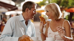 Stock Video Footage of Senior couple sitting in cafe eating croissant and laughing together.