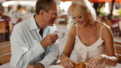 Senior couple sitting in cafe eating croissant and laughing together. - stock footage