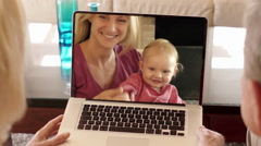 Senior couple enjoying video online with daughter and grandchild. Stock Footage