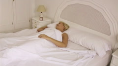 Woman getting out of bed Stock Footage