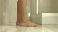 Woman entering shower, view of legs - stock footage