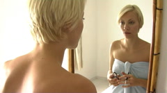 Woman in towel putting on eye makeup Stock Footage