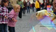 Stock Video Footage of Children amazed by huge soap bubbles on the street