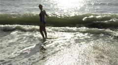 Woman jumping in surf Stock Footage