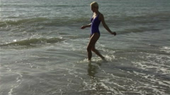 Woman on beach playing in surf Stock Footage