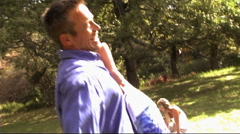 Family in park, father and son swinging around Stock Footage