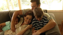 Family on sofa cuddling and tickling Stock Footage