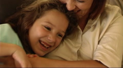 Mother and daughter cuddling on sofa Stock Footage