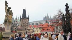 Tourist people on Charles Bridge in Prague, old town buildings Stock Footage