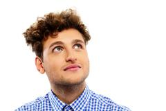 pensive young man with curly hair looking up - stock photo