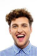 portrait of a young laughing man on white background - stock photo
