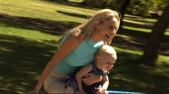 Mother and Baby in Park in roundabout - stock footage