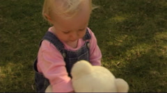 Baby with teddy bear in park - stock footage