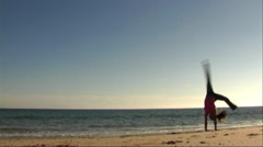 Woman on beach doing acrobatics Stock Footage