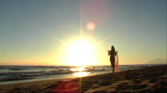 Woman with shawl walking on beach at sunset. - stock footage