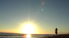 Woman running on beach at sunset with shawl - stock footage