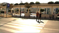 Couple in town crossing road Stock Footage