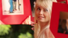 Blonde girl consider the photos in red borders in forest - stock footage