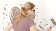 Woman with paint roller painting wall Stock Footage