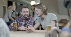 Men sitting and talking in pub - stock footage