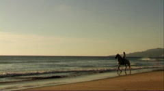 Woman on horse at seashore, riding through surf Stock Footage
