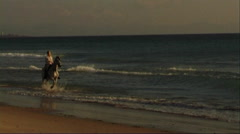 Woman on horse at seashore, riding through surf - stock footage