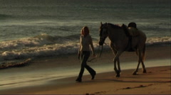 Woman leading horse at seashore, - stock footage