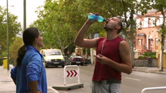 Joggers drinking energy drink, slow motion shot, steadycam shot Stock Footage