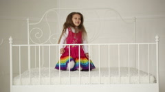 Little girl playing with pillows on the big bed in the bedroom Stock Footage