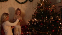 Mother and daughter putting decorations on Christmas Tree. Stock Footage