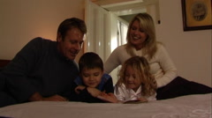 Parents putting children to bed, reading bedtime story - stock footage