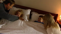 Stock Video Footage of Parents putting children to bed.