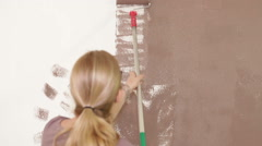 Woman with paint roller painting interior Stock Footage