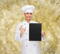 Smiling female chef with black blank paper Stock Photos
