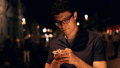 Handsome Young Businessman taping on Smartphone Night Vacation Stock Footage