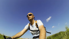 A man rides a bicycle through the countryside - stock footage