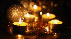 Burning small candles and Christmas tree decorations against a dark background Stock Footage