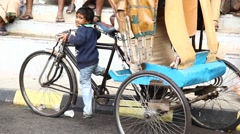 Young boy try to ride rickshaw Stock Footage