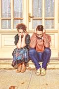 Depressed and agitated man and woman crouching in front of the house at stair Stock Photos