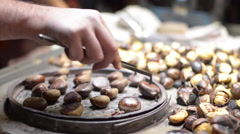 Chestnut roasted cooked street vendor trolley barbecue fast food pedestrians Stock Footage