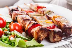 grilled shashlik with vegetables on plate - stock photo