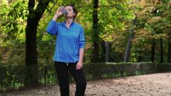 Thirsty woman drinking energy drink, slow motion shot at 240fps, steadycam shot Stock Footage